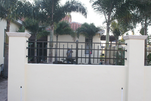 Photo of the courtyard wall built by our general contractor with palms and patio pavers beyond