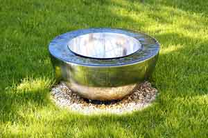 reflective surface bowl style pondless water feature set in a green lawn